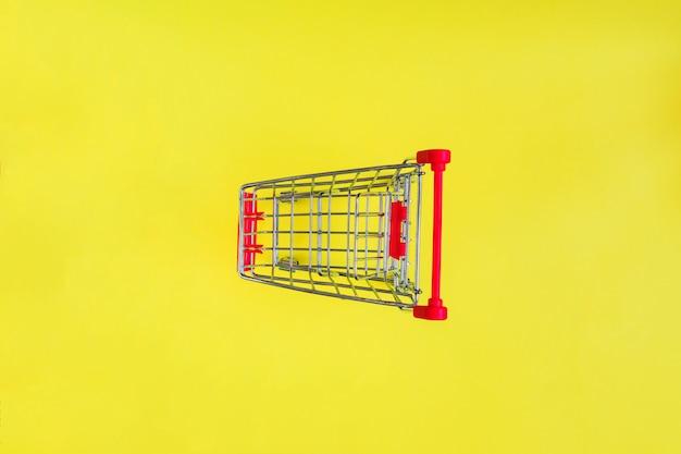 Leerer einkaufswagen auf gelb.