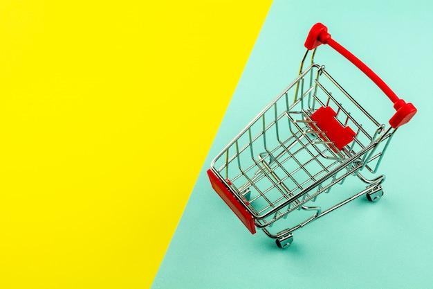 Leerer einkaufswagen auf gelbem und blauem hintergrund
