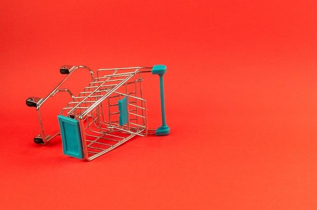 Leerer einkaufswagen auf hellem rotem hintergrund