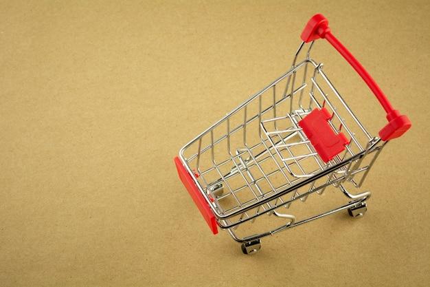 Leerer einkaufswagen auf hintergrund des braunen papiers