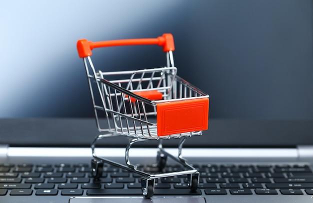 Leerer einkaufswagen aus metall auf laptoptastatur vor dem bildschirm