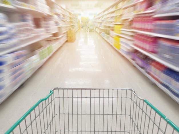 Leerer einkaufswagen des wagens auf der insel mit bewegungsunschärfe des produktregals im supermarkt