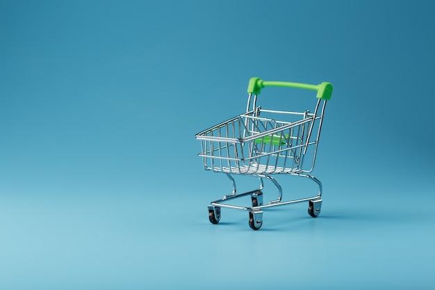 Leerer einkaufswagen für waren aus dem supermarkt auf einer blauen oberfläche.