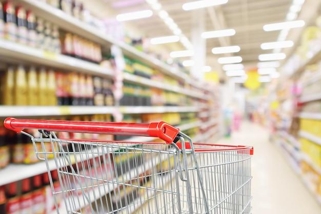 Leerer einkaufswagen mit abstraktem unschärfe-supermarkt-discounter-gang und saucengewürzproduktregalen innen defokussiertem hintergrund
