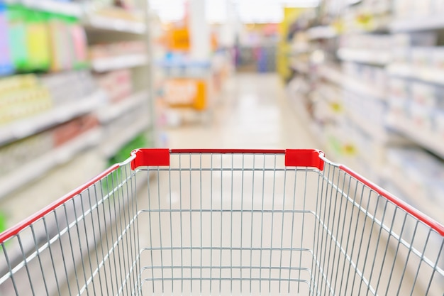 Leerer einkaufswagen mit abstrakter unschärfe supermarkt discounter gang und produktregale innenraum defokussiert hintergrund