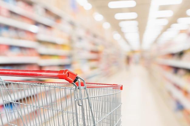 Leerer einkaufswagen mit abstrakter unschärfe supermarkt discounter gang und produktregale