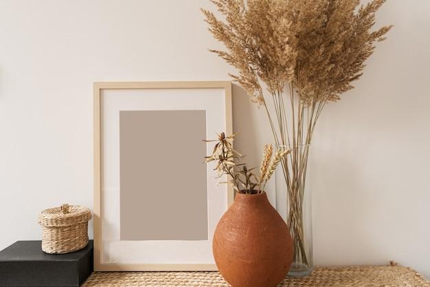 Leerer fotorahmen, flauschiger schilfstrauß in der vase, roggen im tontopf an der weißen wand