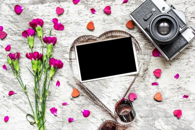 Leerer fotorahmen im herzförmigen film mit retro-kamera und nelkenblumen