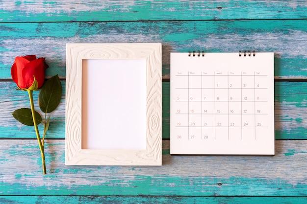Leerer fotorahmen, kalender und rote rosen über holztisch
