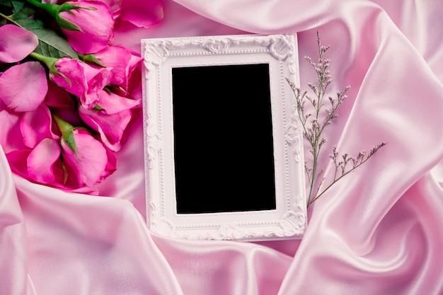 Leerer fotorahmen mit dem rosenblumenblatt des blumenstraußes süßem rosa auf weichem rosa seidengewebe, romance und liebeskartenkonzept