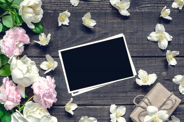 Leerer fotorahmen mit rosen und jasminblüten und geschenkbox über rustikalem holztisch. vintage toning