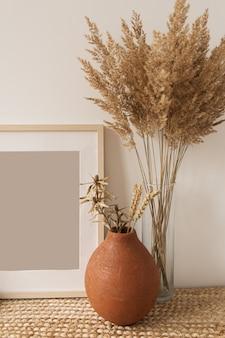 Leerer fotorahmen, schilfstrauß in der vase, roggen im tontopf an der weißen wand