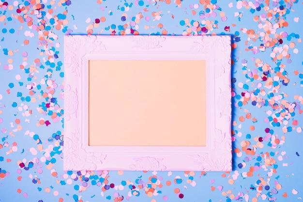 Leerer fotorahmen und dekorative konfettis auf blauem hintergrund