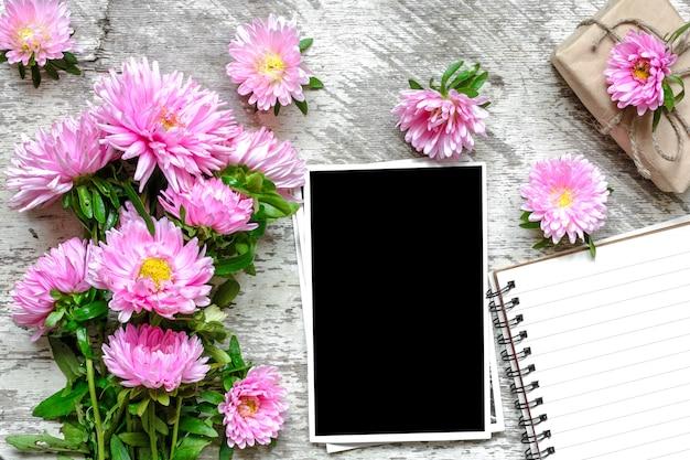 Leerer fotorahmen und notizbuch aus papier mit rosa asterblumen und geschenkbox