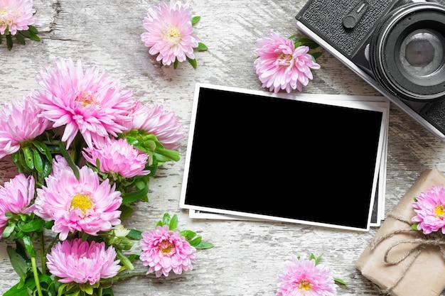 Leerer fotorahmen und retro-kamera mit rosa asterblumen und geschenkbox