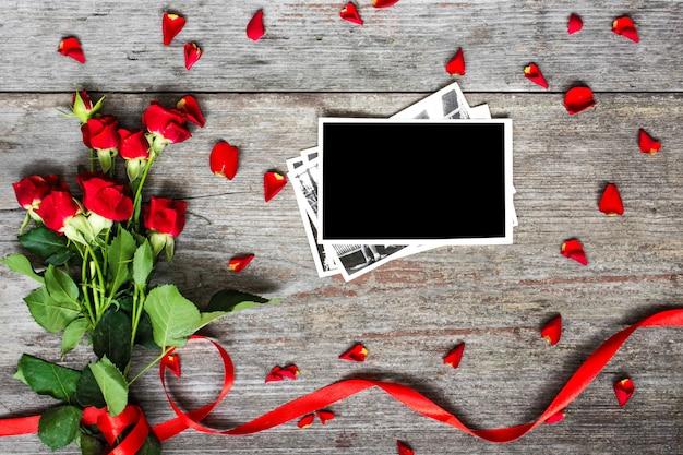 Leerer fotorahmen und rote rosenblumen mit blütenblättern