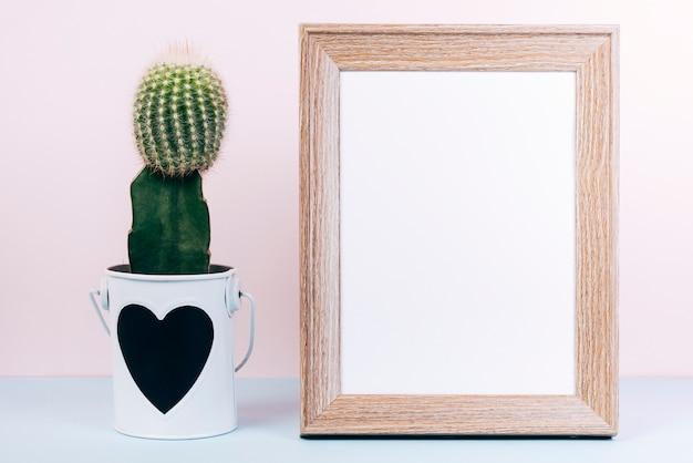 Leerer fotorahmen und saftige anlage mit heartshape auf topf