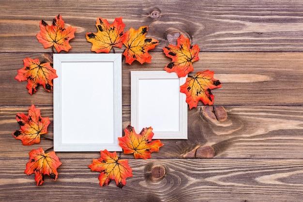 Leerer fotorahmen zwei auf einem braunen holztisch umgeben durch orange ahornblätter. kopieren sie platz