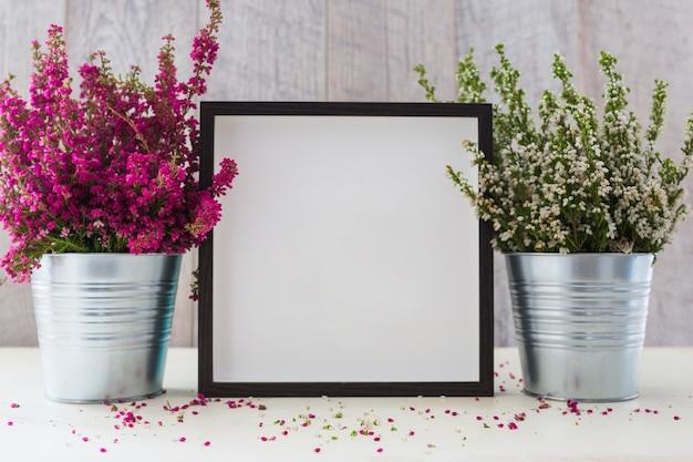 Leerer fotorahmen zwischen den zwei aluminiumtopf mit kleinen blumen auf schreibtisch