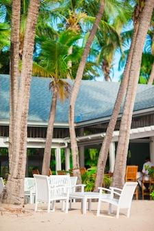 Leerer freilichttisch des sommers stellte für bankett auf tropischem karibischem strand ein