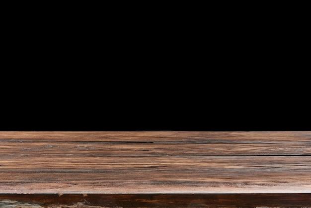 Leerer gealterter strukturierter eichenholztisch auf einem schwarzen hintergrund für geschenk und montage ihrer produkte und sachen. verwenden sie das stapeln des fokus, um die volle schärfentiefe zu erzielen.
