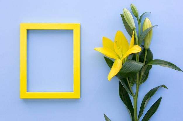 Leerer gelber fotorahmen mit lilie blüht auf blauer oberfläche