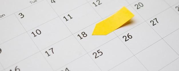 Leerer gelber klebriger klebepfosten auf kalender