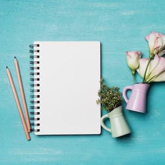 Leerer gewundener notizblock mit zwei bleistiften und vasen auf strukturiertem blauem hintergrund