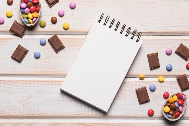 Leerer gewundener notizblock zwischen den edelsteinen und schokoladenstücken auf hölzernem schreibtisch