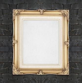 Leerer goldfarbweinlese-fotorahmen, der an der schwarzen backsteinmauer, schablone für das addieren ihres fotos hängt