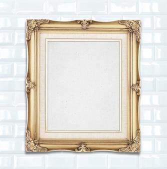 Leerer goldfarbweinlese-fotorahmen, der an der weißen keramikziegelwand, schablone für das addieren ihres fotos hängt