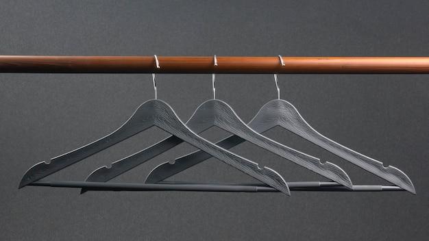 Leerer grauer plastikkleiderbügel, der auf einem dunklen hintergrund hängt. zubehör und gegenstände zur aufbewahrung von kleidung.