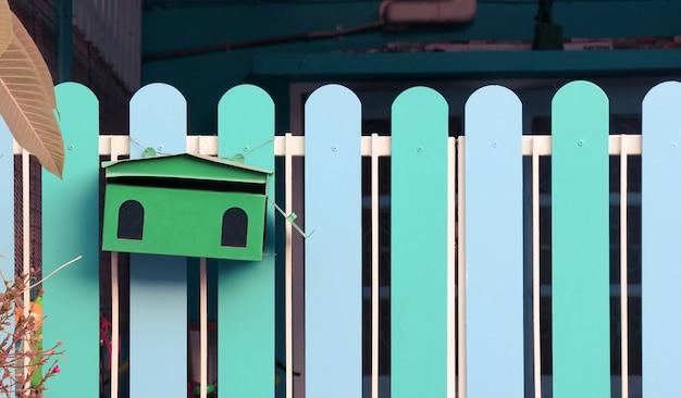 Leerer grüner briefkasten auf dem blauen zäuntürhintergrund