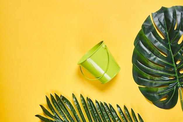 Leerer grüner eimer mit griff und palmblättern