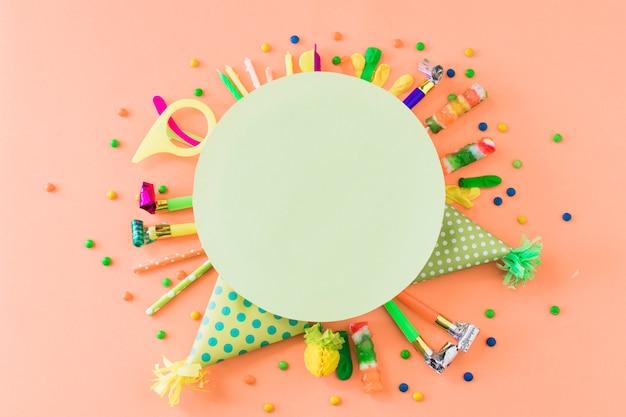 Leerer grüner rahmen über partyzubehör und -süßigkeiten auf orange hintergrund