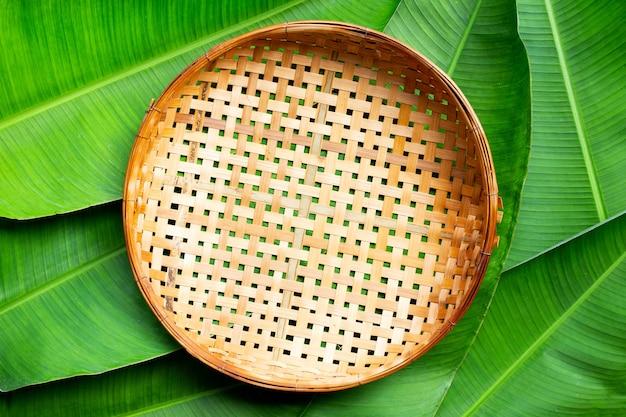 Leerer hölzerner bambusdreschkorb auf bananenblättern hintergrund. draufsicht