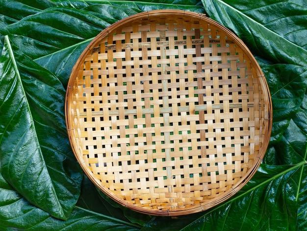 Leerer hölzerner bambusdreschkorb auf noni oder morinda citrifolia hinterlässt hintergrund. draufsicht