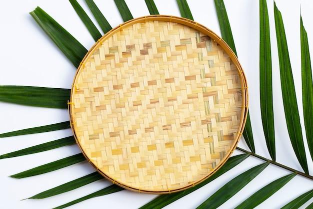 Leerer hölzerner bambusdreschkorb auf tropischen palmblättern auf weißem hintergrund.