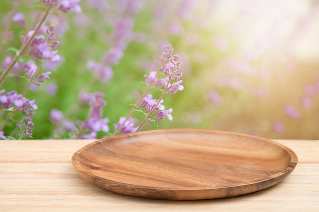 Leerer hölzerner behälter auf perspektiveholztisch auf die oberseite über unschärfeblumenhintergrund.