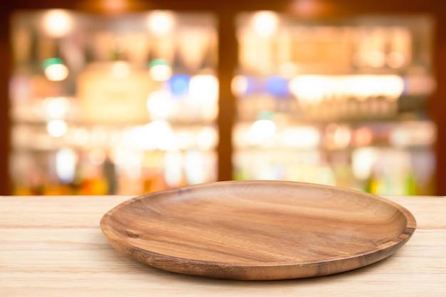 Leerer hölzerner behälter auf perspektiveholztisch auf die oberseite über unschärfes weinbar im caféhintergrund