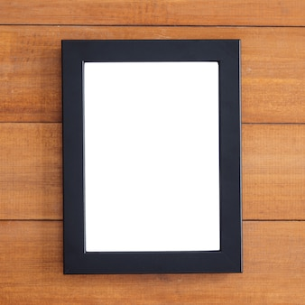 Leerer hölzerner bilderrahmen auf dem tisch. kann für ihren text oder ihr kunstwerk verwendet werden. draufsicht