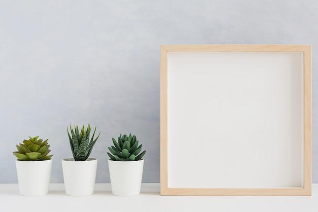 Leerer hölzerner bilderrahmen mit art drei eingemachter kaktuspflanze auf schreibtisch