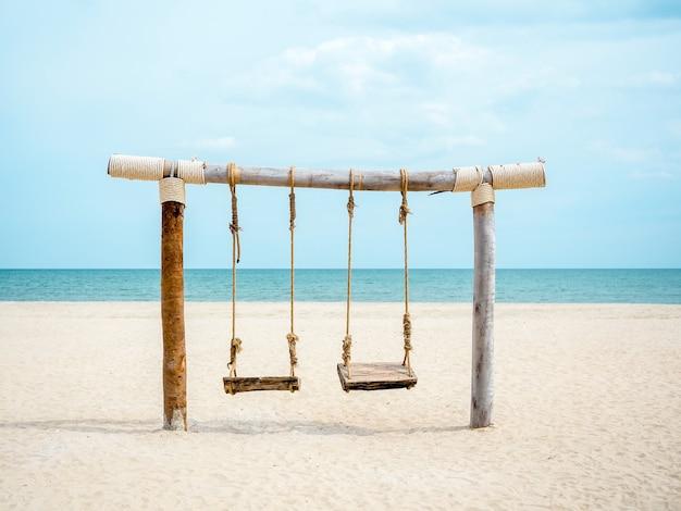 Leerer hölzerner doppelschaukelsitz am strand auf seelandschaft, sand, meer und blauem himmel