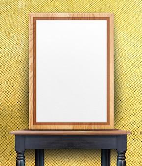Leerer hölzerner fotorahmen, der an der goldmosaikfliesenwand auf hölzerner tabelle der schwarzen weinlese sich lehnt