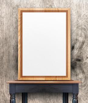 Leerer hölzerner fotorahmen, der an der hölzernen wand auf hölzerner tabelle sich lehnt