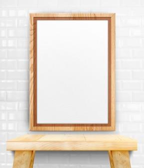 Leerer hölzerner fotorahmen, der an der weißen fliesenwand auf hölzerner tabelle hängt.