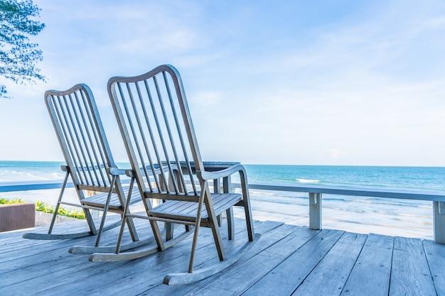 Leerer hölzerner stuhl und tabelle am patio am im freien mit schönem tropischem strand und meer