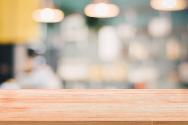 Leerer hölzerner tischplatte-aufnahmezähler oder bargeld-zähler auf unscharfem hintergrund für das montageprodukt vorhanden