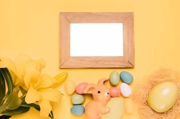 Leerer hölzerner weißer rahmen mit ostereiern; häschennest und lilienblume auf gelbem hintergrund