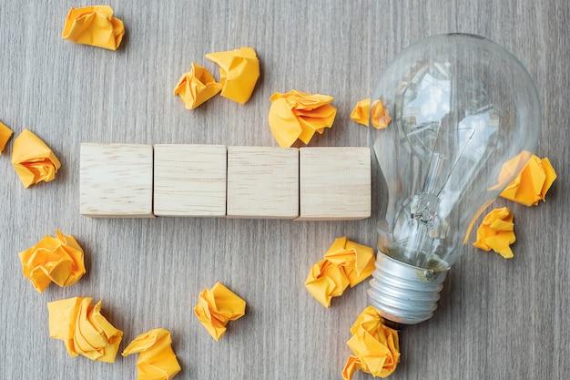Leerer hölzerner würfel und zerfallenes papier mit glühlampe